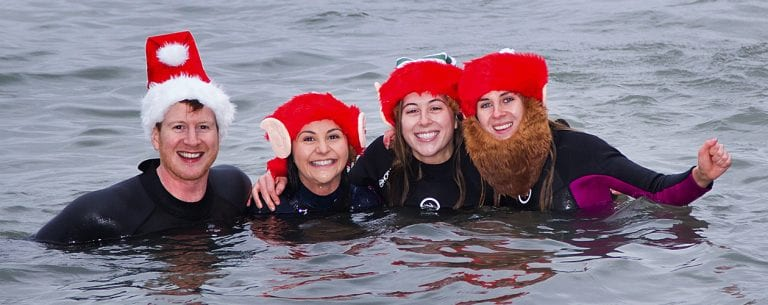 Swimmers enjoy a dip in the tide at the annual charity Christmas Day Swim